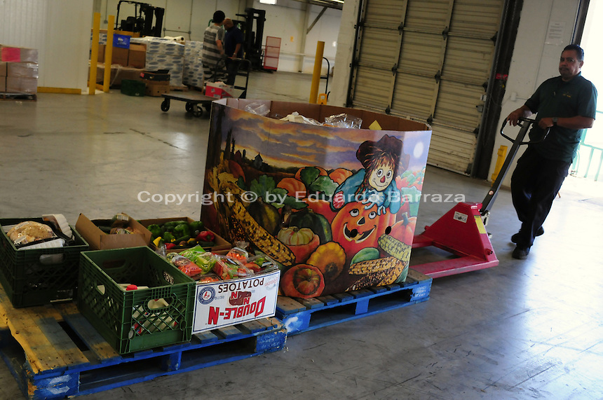 Phoenix, Arizona. October 18, 2012 - Gabriel Mendoza brings in a load of donated food that was just brought to the United Food Bank warehouse by a delivery truck driver. The goods will be inspected, sorted and packaged and then delivered to community agencies who provide food boxes. As the amount of food donations decreases, food banks such as the United Food Bank strive to keep up with hunger relief needs of 1 in 5 (20%) of Arizonans who are living in poverty and, based on figures of the Department of Health and Human Services. Photo by Eduardo Barraza © 2012