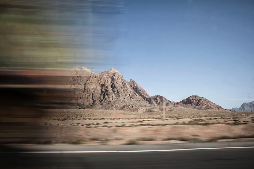 A truck passes by revealing the mountain range as seen during the ride along the desert road of Central Iran, near Yazd.