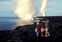 Spectators watch as lava flows into the sea. Hawaii Volcanoes National Park, Big Island