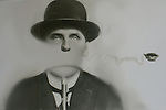 A man wearing bowler hat with no mouth