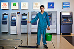 """June 2012, Ramallah, West Bank. Mohammad, 16,  works for the cleaning company """"Wipe and shine""""  in a new shopping mall in Al Bireh. This year he will pass the high school final exam. In Palestine, cleaning companies are quite a new thing, as the structure of companies is traditionally based on family membership. In the  background, the ATM of some of 17 banks existing in Palestine in 2012, of which 7 are Palestinian Banks."""