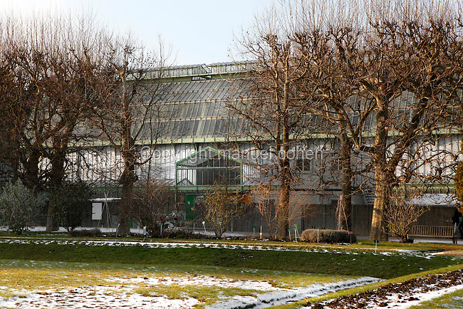 Desert and Arid Lands Glasshouse, 1930s, Jardin des Plantes, Museum National d'Histoire Naturelle, Paris, France, adjoining the Tropical Rainforest Glasshouse (formerly Le Jardin d'Hiver or Winter Gardens), 1936, René Berger. Low angle view showing the snowy lawns and bare trees of the Jardin des Plantes in front of the glasshouses in winter.