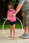Old Westbury, New York, U.S. 22nd June 2013. A young girl is learning to play with an old-fashioned wood hoop and stick at the Midsummer Night event at Old Westbury Gardens, on the grounds of the historic Long Island Gold Coast estate.