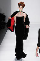 Model walks runway in a black silk velvet strapless movie star gown w/back -panel, black saga royal fox moie star stole lined w/ruby silk gazar+satin imperial frame, from the Zang Toi Fall 2012 &quot;Glamour At Gstaad&quot; collection, during Mercedes-Benz Fashion Week New York Fall 2012 at Lincoln Center.