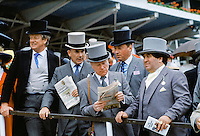 Racegoers in traditional top hats and tails reading the racing news at Epsom Racecourse on Derby Day, UK