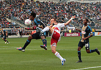 CHESTER, PA - OCTOBER 27, 2012:  Amobi Okugo (14) of the Philadelphia Union leaps into the way of  Joel Lindpere (20) of the New York Red Bulls during an MLS match at PPL Park in Chester, PA. on October 27. Red Bulls won 3-0.