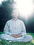 Shaolin monk meditating outdoors during sunrise in sunlight