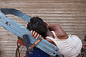 A peddle rickshaw driver sleeping and resting in between work. Old Delhi, New Delhi, India