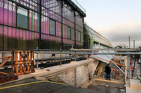 New Caledonia Glasshouse (formerly The Mexican Hothouse), 1830s, Charles Rohault de Fleury, Jardin des Plantes, Museum National d'Histoire Naturelle, Paris, France. General view showing an access ramp being built in front of the glass and metal structure, which is reflecting the late afternoon light. Beyond it is the Art Deco style Tropical Rainforest Glasshouse (formerly Le Jardin d'Hiver or Winter Gardens), 1936, René Berger. The New Caledonia Glasshouse, or Hothouse, was the first French glass and iron building.