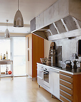 This industrial looking extractor duct gives this kitchen a professional feel