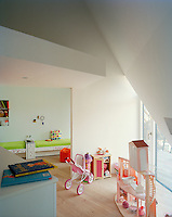 The colourful nursery is filled with toys and has a contemporary doll's house in the foreground