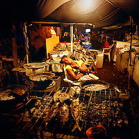 A woman selling fish from a stall on the Ilha de Luanda sleeps while she waits for customers.