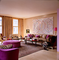 The swirling artwork on one wall of the living room echoes the pink and gold palette used in its decoration