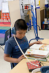 Oakland CA 2nd grader using audio equipment to facilitate reading
