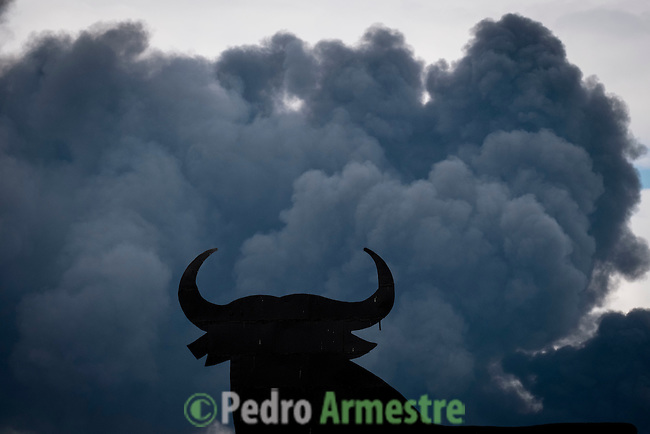The shape of an 'Osborne Bull' is pictured with black clouds of smoke on the background, produced by tyres burning in an uncontrolled dump near the town of Sesena, after a fire broke out early on May 13, 2016. A huge waste ground near Madrid where millions of tyres have been dumped was on fire today, releasing a thick black cloud of toxic fumes that officials worry could harm residents nearby.  © Pedro ARMESTRE