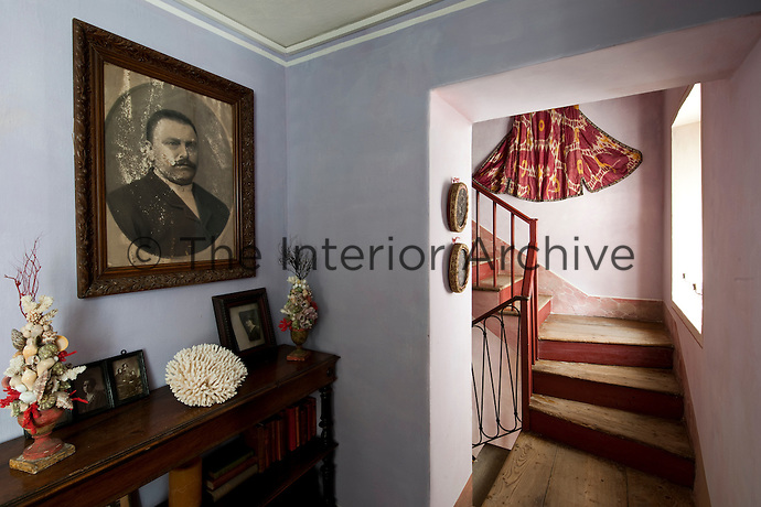 An old family portrait hangs on the pale purple wall of an upstairs landing
