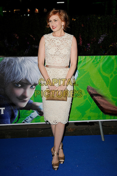 Isla Fisher.Attending the UK Premiere of 'Rise Of The Guardians', Empire Cinema, Leicester Square, London, England, UK. 15th November 2012..full length sleeveless white cream lace peplum dress clutch bag gold silk satin beige ribbon waistband shoes .CAP/MAR.© Martin Harris/Capital Pictures.