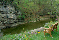 Wooden bench for two overlooking grindstone creek and the facing bluffs in spring season