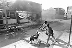 A woman with her children walk past several burn out businesses on South Vermont Ave. in South Central Los Angeles..Los Angeles has undergone several days of rioting due to the acquittal of the LAPD officers who beat Rodney King..Hundreds of businesses were burned to the ground and over 55 people have been killed.