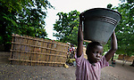 "A girl carries water home from the village pump in Chidyamanga, a village in southern Malawi that has been hard hit by drought in recent years, leading to chronic food insecurity, especially during the ""hunger season,"" when farmers are waiting for the harvest."