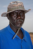 Millet Cultivation.  Senior Family Member of the Family Owning the Land at this location.  He is a member of the Serer ethnic group.  Kaolack, Senegal.