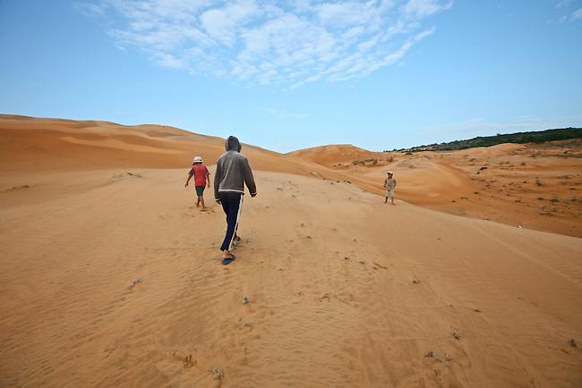 Children walk across the red dunes near Mui Ne, Vietnam. Nov. 11, 2011.