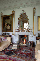 The elaborate neo-classical chimneypiece designed by Giacinto Micali draws the eye up to the equally ornate plasterwork ceiling