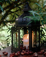 Detail of an outdoor lantern with a burning candle inside