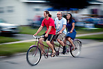Riding a three-person bike around a Madison, Wisconsin's Warner  Park before the start of a 4th of July celebration. ..