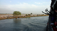 Dinka tribespeople on a barge returning displaced persons from Juba to their homeland of Bor after the civil war wave as they pass a settlement on the edge of the River Nile.  The resettlement programme is organised by the IOM (International Organisation for Migration).  Tens of thousands of Dinka tribespeople are among the estimated 3.8 million people displaced during the two-decade long conflict between the government and the SPLA (Sudanese People Liberation Army)...