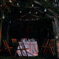 A table is draped in a simple cloth and surrounded by bamboo garden chairs under a rustic rose arbour lit with candles