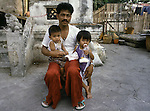 A father poses with his two children while his wife works in a booth selling bootleg watches and bags to tourists that visit the Wat Po temple complex  in Bangkok, Thailand. (Jim Bryant Photo).....