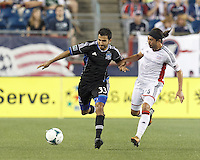 San Jose Earthquakes defender Steven Beitashour (33) brings the ball forward as New England Revolution midfielder Lee Nguyen (24) defends. In a Major League Soccer (MLS) match, the New England Revolution (white) defeated San Jose Earthquakes (black), 2-0, at Gillette Stadium on July 6, 2013.