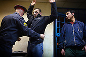 A policeman searches a Georgian worker before putting him and a Tajik worker (right) in prison after they were arrested for working without a permit in Moscow. Russia is cracking down on foreign nationals working in its markets and construction sites.