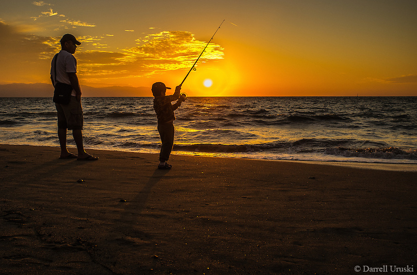 Little boy fishing during a golden sunset in mexico for Father son fishing