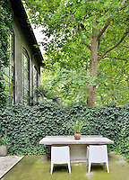 A stone table and two white chairs are set on a stone patio area of a garden. A screen of ivy provides privacy.