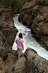 A woman stands on a cliff above the Rogue River as it rushes through Takelma Gorge, Rogue River National Forest, Oregon