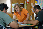 Randie Clawson, a member of United Methodist Women from Traverse City, Michigan, teaches a class in English as a Second Language at the Posada Providencia, a shelter in San Benito, Texas, for people in crisis from all over the world who are seeking legal refuge in the United States. The shelter is sponsored by the Catholic Sisters of Divine Providence. The two men are from Pakistan.