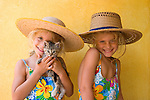 Mexico.  Twins pose in hats for the camera with their small kitten. MR