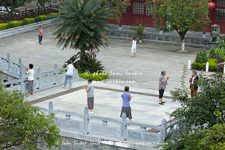 Group of mature women practicing tai chi chuan in a courtyard early in the ...