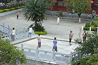 Group of mature women practicing tai chi chuan in a courtyard early in the morning, Yangshuo, Guangxi, China.