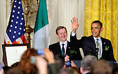 United States President Barack Obama (R) waves as he concludes remarks with Irish Prime Minister Enda Kenny who presented Obama with a certificate of Irish heritage (L) during a reception in the East Room of the White House, March 20, 2012, in Washington, DC. The two leaders concluded a working day devoted to discussions on economic matters, Ireland's peace keeping participations and foreign policy issues like Syria and Iran.   .Credit: Mike Theiler / Pool via CNP