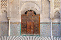 Carved wooden door in the central courtyard of the Al-Attarine Madrasa, a religious school built 1323-25 by the Marinid Sultan Uthman II Abu Said, who ruled 1310-31, in the medina of Fes, Fes-Boulemane, Northern Morocco. The door is surrounded by intricate carved stucco work and zellige tiles in decorative geometric designs on the lower walls and floor. The medina of Fes was listed as a UNESCO World Heritage Site in 1981. Picture by Manuel Cohen