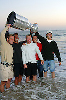 24 August 2002: Detroit Red Wings professional hockey players JIRI FISCHER, CHRIS CHELIOS, KRIS DRAPER, SEAN AVERY & LUC ROBITAILLE hold the  NHL Stanley Cup over their head away from the surf at sunset on the beach in the Pacific Ocean in front of Chris's summer Malibu home in Los Angeles. .
