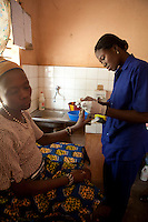 "9 December 2009, Banikoara, Benin. Community Health Clinic ""Comparou Maternité."" The clinic delivers a wide variety of services including delivering of babies and ante-natal checkups. The mothers-to-be are given an ante-natal package of folic acid, mosquito nets and malaria prophylactics. If there is an emergency, an ambulance can take them to the main hospital. 30 year-old housewife Nowiatau Alidau is about 8 months pregnant with her third child."
