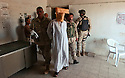 """Members of a U.S. Army Special Forces (SF) """"A-team"""" and U.S. Military Police take a captured high level Saddam Fedayeen leader into custody in the town of Samarra, Iraq August 21, 2003."""