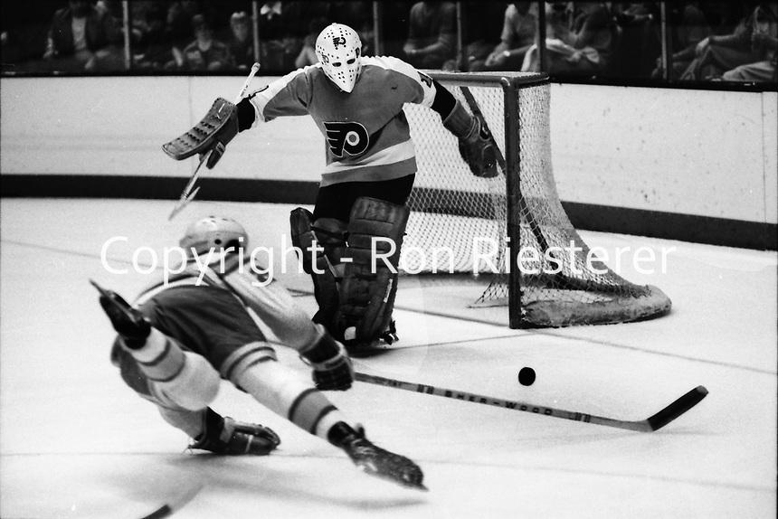 Seals #2 Rick Hampton shoots on Philadelphia Flyer golie Bernie Parent. (1975 photo/Ron Riesterer)