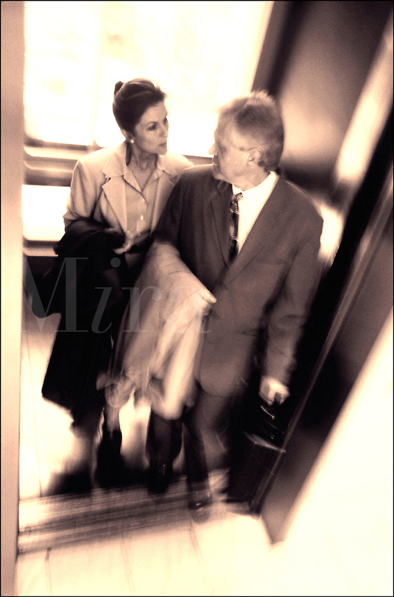 Business man and woman getting off an elevator