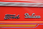 Bellmore, New York, USA. May 29, 2015. 1940 Red Ford Coup has chrome Ford Deluxe emblems and colorful pinstripe detailing at the Friday Night Car Show held at the Bellmore Long Island Railroad Station Parking Lot. Hundreds of classic, antique, and custom cars are generally on view at the free weekly show, sponsored by the Chamber of Commerce of the Bellmores, from May to early October.