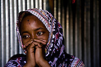 Siida Noor Ahmed, 29 years old. Siida fled Mogadishu with 7 of her ten children and arrived  at State House IDP camp in January 2009. Her husband and 3 of her children disappeared during recent fighting in Mogadishu. .At state house she is being helped by long term resident Koos Aw Dahir with  rent, food and childcare. Koos was one of the original  residents of state house and recognized somthing of her own struggle in Siida's story..According to Siida &quot;I came here to get peace and to keep my children.  Three of my children went to school one day in Mogadishu.  There was fighting at the school so they ran away and got lost.  I don't know if they're alive or dead.  It's part of my body which is missing.  If only I could be told my children are dead - I could give up.&quot;.  .&quot;Nobody normal lives in Mogadishu now - they're all abnormal.  Sometimes you see people in groups - after a few minutes a section of a person is brought back in pieces.  Sometimes people bring back the head of a friend saying 'I found a head.'&quot;..&quot;It's luck to eat.  People go into Mogadishu in search of casual work.  Sometimes they're given a bag to carry somewhere for 20,000 Somali shillings. But the bag is a bomb.  When they reach the destination, the person who gave it to them detonates it.&quot;..&quot;It was very hard to leave.  I didn't know where I was going.  My problem here is a lack of food.  How do you feel when you rely on people - when you go and ask 'have you cooked?'  Imagine how that feels if you've been working before.  We feel like we're becoming a problem to the neighbours.&quot;..&quot;But we're happy because we have peace, people here have given us a house and the lady next door is helping me.&quot;  .